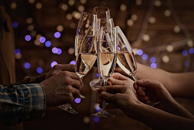 Clinking-glasses-of-champagne-in-hands-on-bright-lights-background